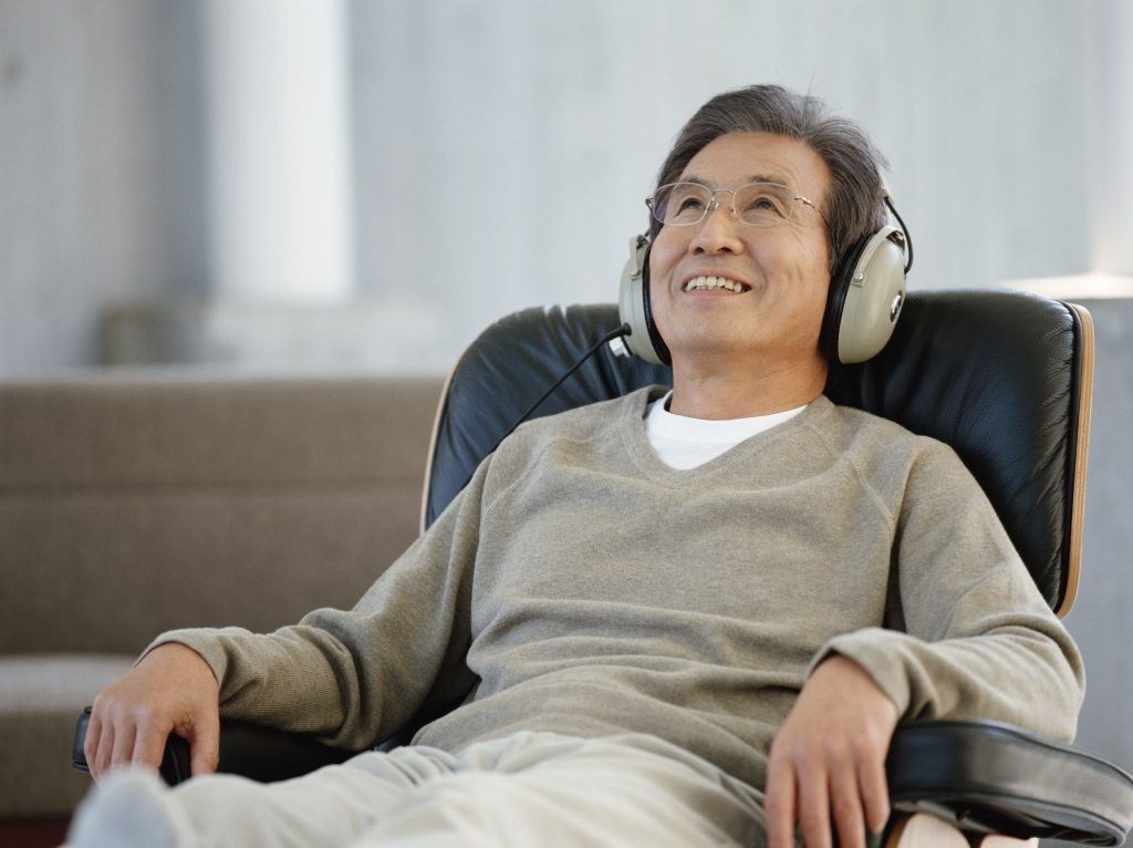 A man sits during an alcohol addiction research session while listening to a comedy show with headphones on.