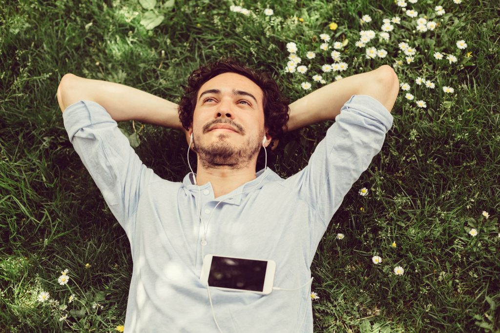 A man relaxes on the grass and thinks about alcoholism therapy and the benefits he's experienced from participating in a montreal rehab program